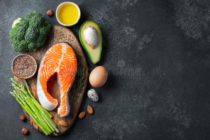A set of healthy food for keto diet on a dark background. Fresh raw salmon steak with flax seeds, broccoli, avocado, chicken eggs. Nuts and asparagus on a stock photography