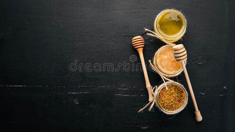 A set of honey and bee products. Honey in honeycomb. On a black wooden background. Free space for text. stock photos