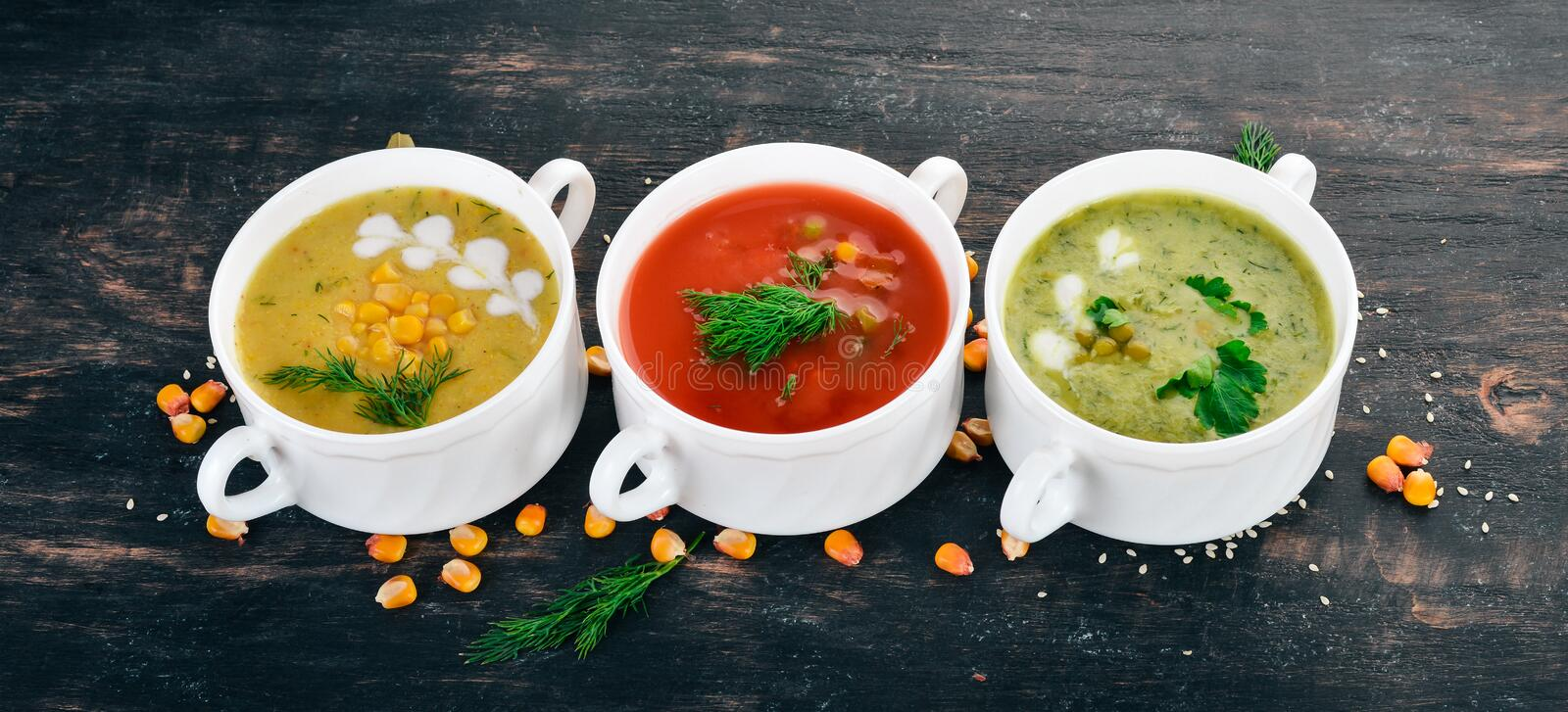 Set of hot, colored vegetable soups. Broccoli soup, corn, tomato soup. Healthy food. On a black wooden background. Copy space royalty free stock photo