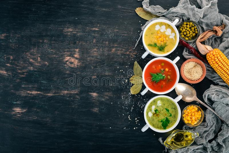 Set of hot, colored vegetable soups. Broccoli soup, corn, tomato soup. Healthy food. On a black wooden background. Copy space stock image
