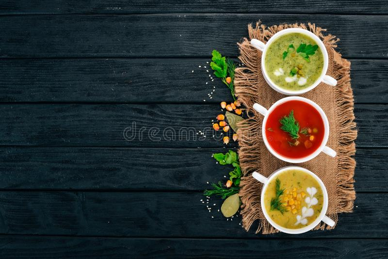 Set of hot, colored vegetable soups. Broccoli soup, corn, tomato soup. Healthy food. On a black wooden background. Copy space royalty free stock image