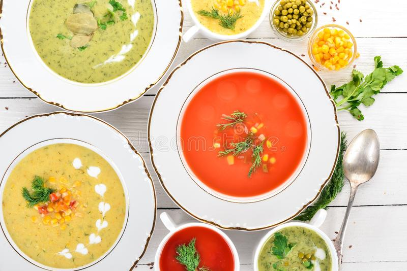 Set of hot, colored vegetable soups. Broccoli soup, corn, tomato soup. Healthy food. On a white wooden background. Copy space royalty free stock images
