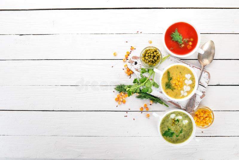 Set of hot, colored vegetable soups. Broccoli soup, corn, tomato soup. Healthy food. On a white wooden background. Copy space royalty free stock photography