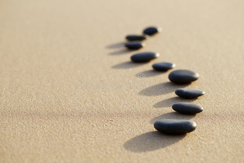 Set of hot stone on white sand calm beach in backbone shape. selective focus, spa concept royalty free stock image