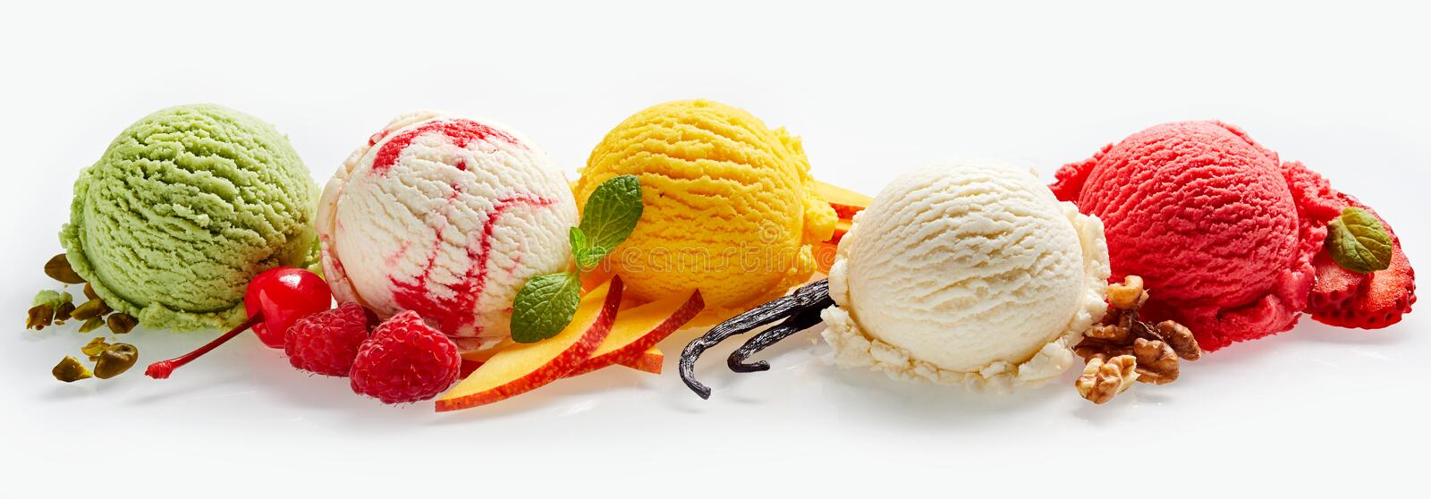 Set of ice cream scoops. Of different colors and flavours with berries, nuts and fruits decoration on white background stock photography