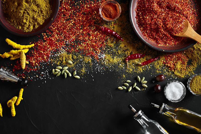Set of indian spices on black background - green cardamom, turmeric powder, coriander seeds, cumin, and chili, top view royalty free stock photos
