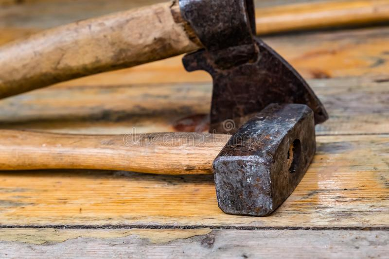 Set of iron tools ax hammer close-up old wooden handle weathered on boards stock photography