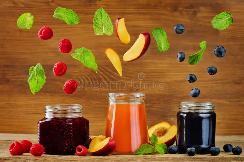Set of jams with flying slices: raspberry, blueberry and peach. Toning. selective Focus royalty free stock photo