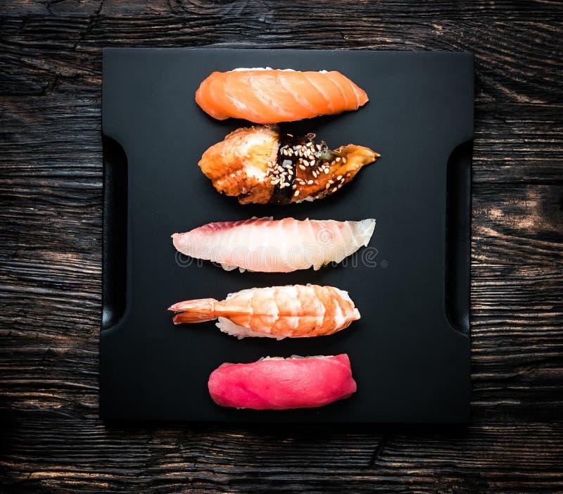 A set of japanese sushi sashimi on black tray. Top view royalty free stock photos
