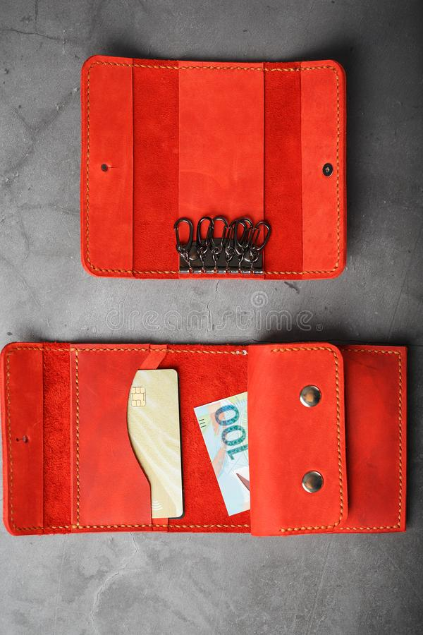 Set of key holder wallet with money and electronic cards and a key holder made of genuine red leather, handmade on a dark. Background. Close-up royalty free stock images