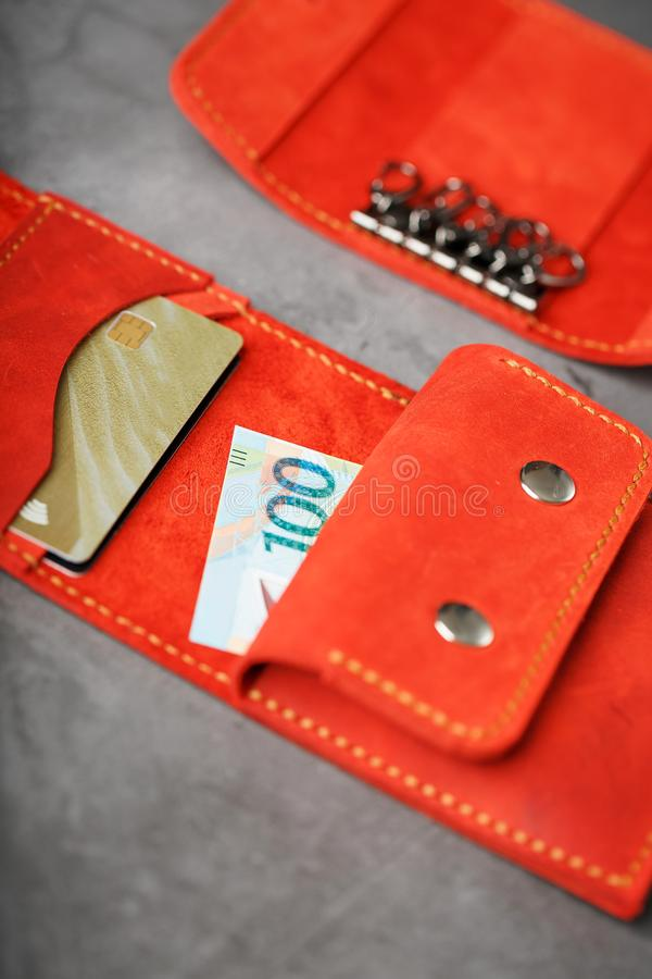 Set of key holder wallet with money and electronic cards and a key holder made of genuine red leather, handmade on a dark. Background. Close-up stock image