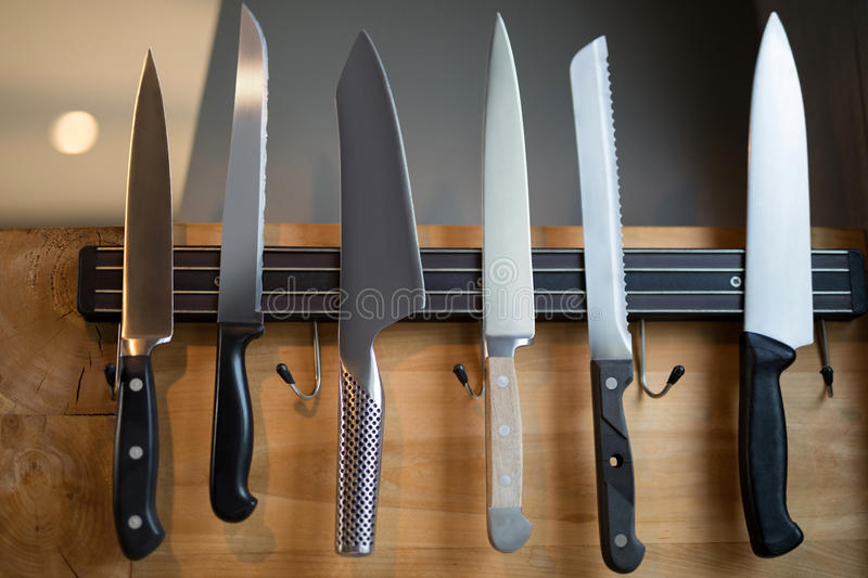 Set of kitchen knives hanging on the wall. Close-up of kitchen knives hanging on the wall royalty free stock photos