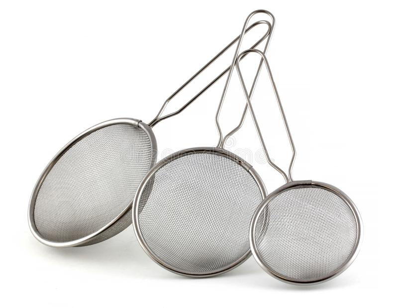 Set of kitchen strainers of different sizes on a white background. The smallest tea strainer and the largest for rice or pasta royalty free stock photography