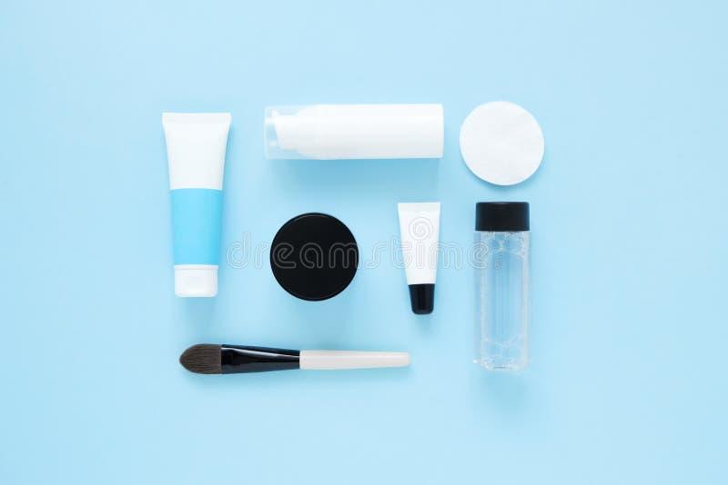 Set kosmetyczni produkty na błękitnym koloru tle, mieszkanie kłaść z przestrzenią dla teksta Biel ruruje, oznakujący egzamin prób obrazy stock