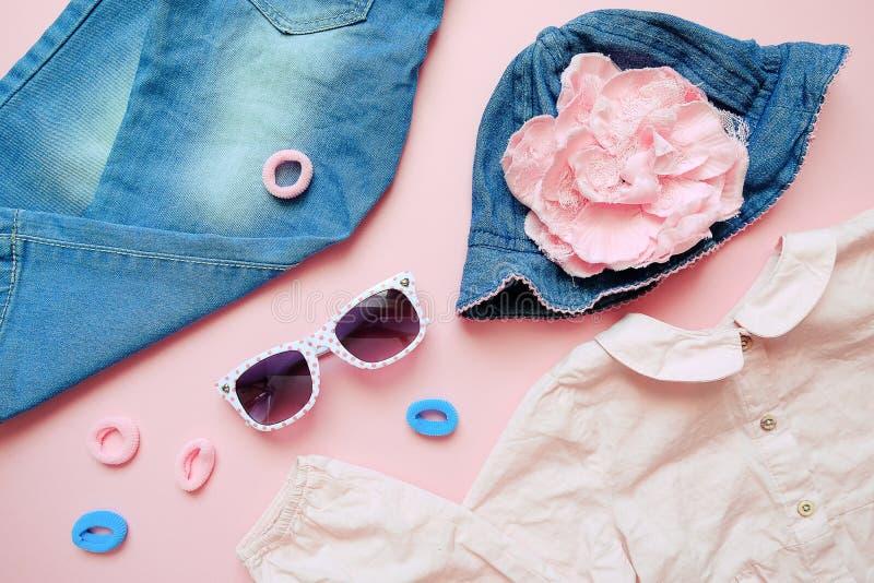 Set lat dzieci odzież na różowym tle Dziewczynki mody spojrzenie z drelichowymi cajgami, koszula, kapeluszem i szkłami, obraz stock