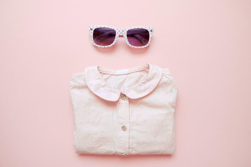Set lat dzieci odzież na różowym tle Dziewczynki mody spojrzenie z koszula i szkłami zdjęcie stock
