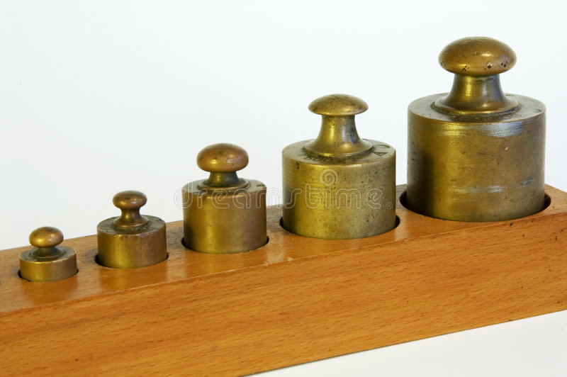 A set of lead weights. In a shaped wooden box stock photography