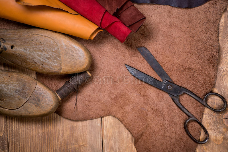 Set of leather craft tools on wooden background. Workplace for shoemaker. Piece of hide and working handmade tools on a work table stock photos