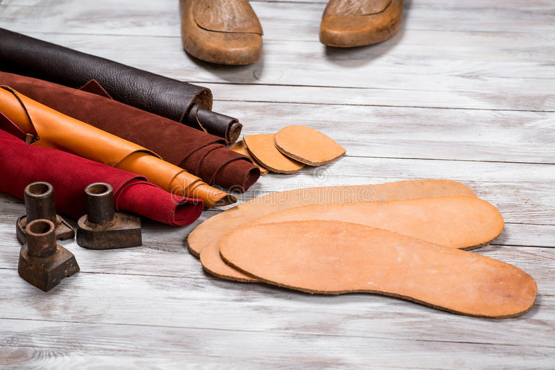 Set of leather in rolls, craft tools on white wooden background. Workplace for shoemaker. Working handmade tools on a work table. royalty free stock photos