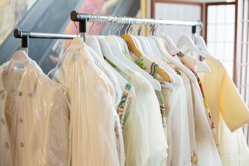 Set of light colored dresses on a wooden hangers.  royalty free stock image