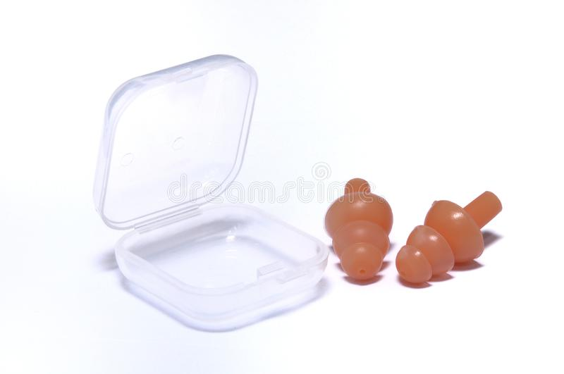 A set of light orange colored silicone ear plugs stock images