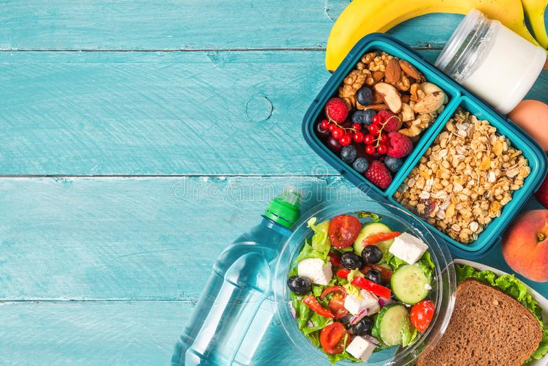 Set of lunch boxes with food ready to go for work or school. greek salad, sandwich, vegetables, granola, nuts, berries stock photography