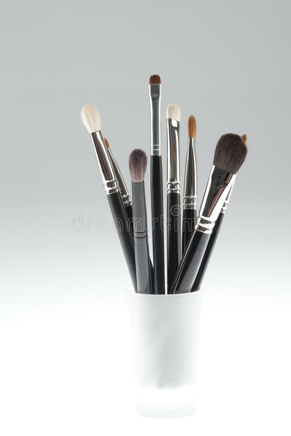 A set of make-up brushes set in a small glass royalty free stock photography