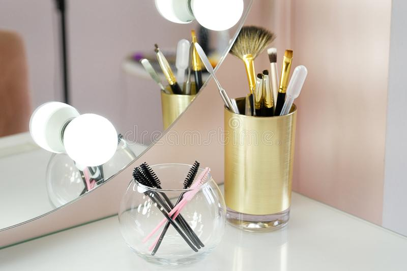 A set of makeup artist brushes for professional makeup on a white table in front of the mirror in the beauty salon, the Concept of royalty free stock photo
