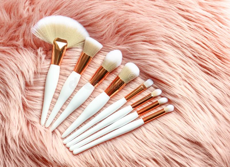 Set of makeup brushes on faux fur. Flat lay stock images