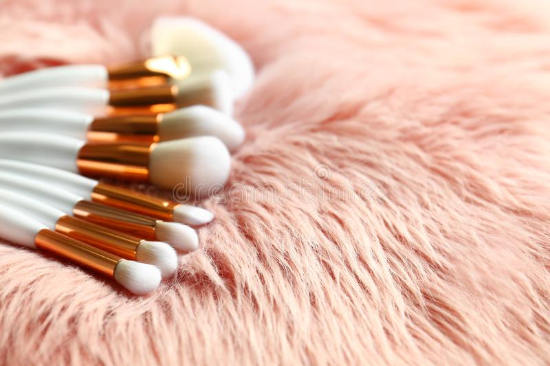 Set of makeup brushes on faux fur. Space for text stock photography