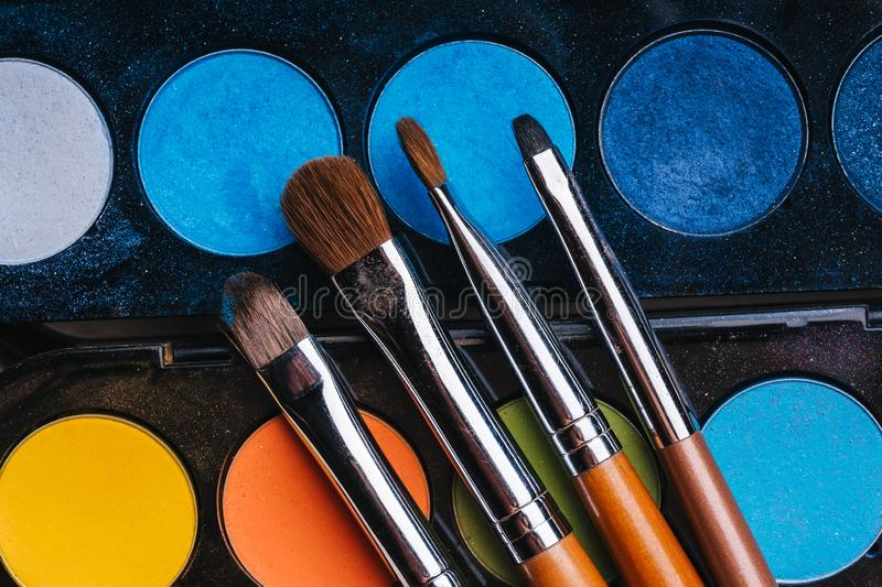 Set of makeup brushes on a palette with colorful eye shadows royalty free stock photos