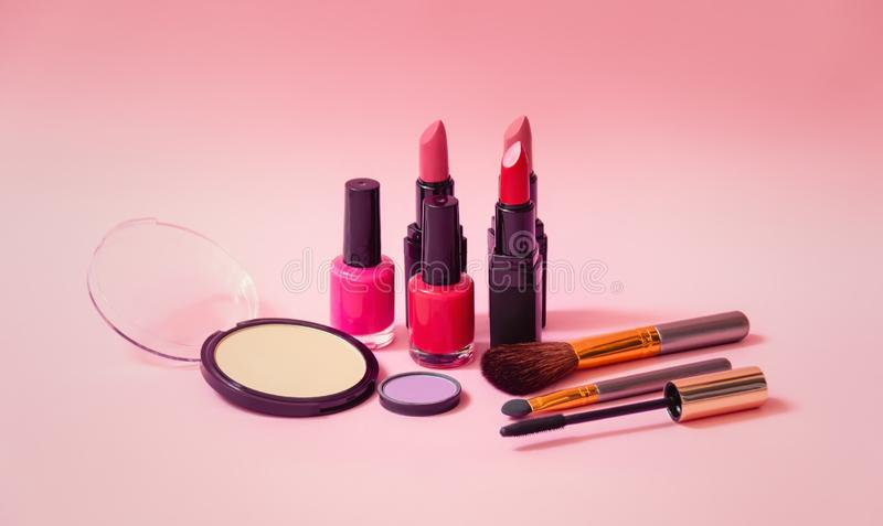 Set of makeup cosmetics, nail polishes and brushes on pink background. Selective focus royalty free stock images
