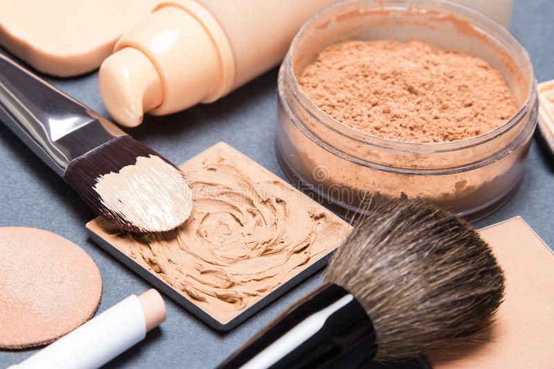 Set of makeup products to even out skin tone and complexion. Set of makeup products and accessories to even out skin tone and complexion. Shallow depth of field stock images