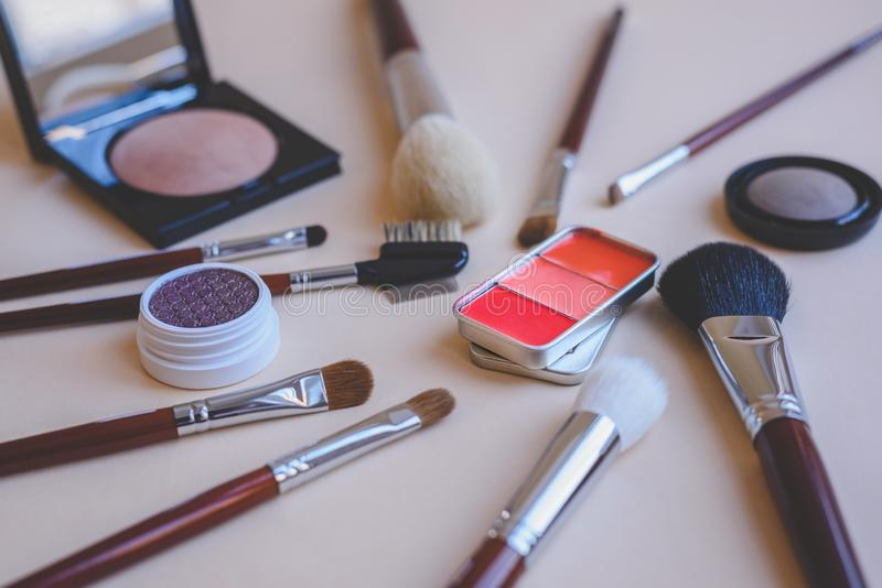 Set of makeup products with various cosmetic brushes a palette of red lipstick in a vintage metal box eye shadow and compact pow stock photos