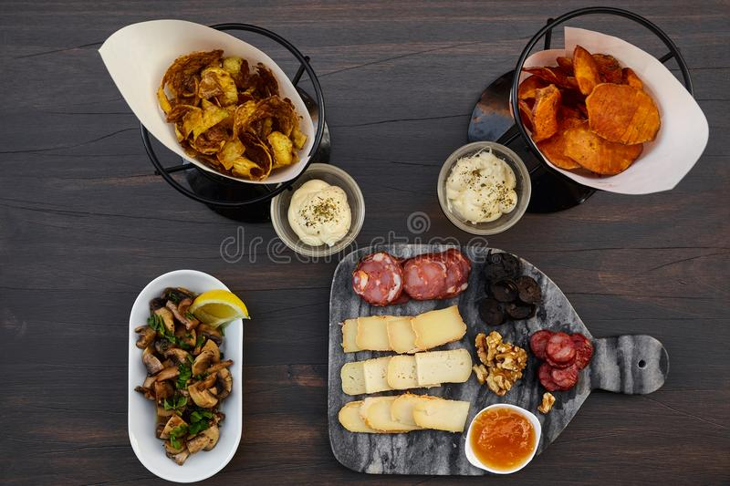 Set of many snacks for wine or beer: several kinds of cut cheeses, sliced smoked sausages, blood sausage, walnuts and apricot sauc royalty free stock photos