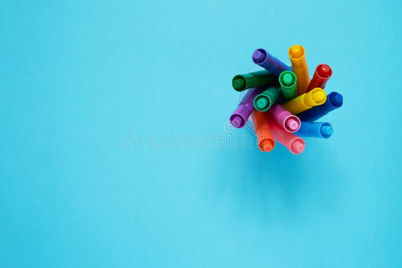 Set of markers in a cup and on light blue background. Top view. Back to school concept.  royalty free stock images