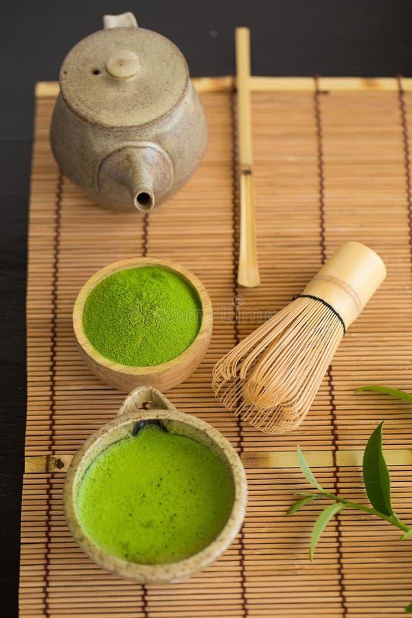 Set matcha proszka pucharu drewniana łyżka i śmignięcie zielona herbata leaf fotografia royalty free