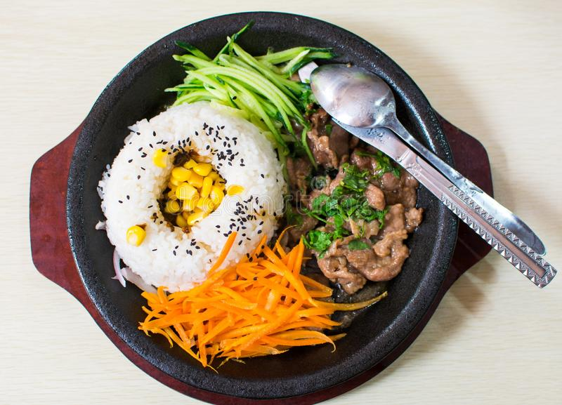 A set of meal with rice, beef, cucumber and carrot served on the. A set of asian meal with rice, beef, cucumber and carrot served on the dark plate royalty free stock images