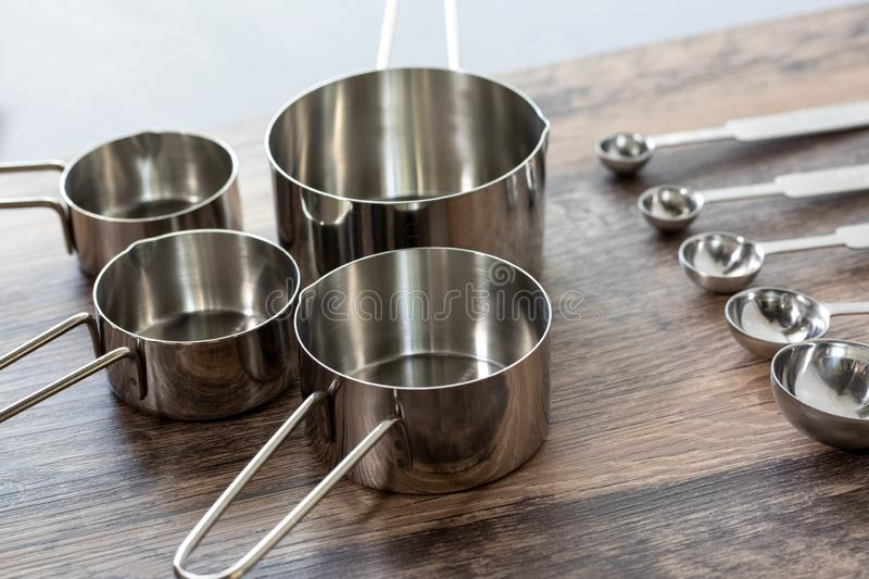 Set of measuring cups and measuring spoon with a handle made from stainless on wooden tabletop in eye level shot. Cooking at home is a happy life style for royalty free stock photos