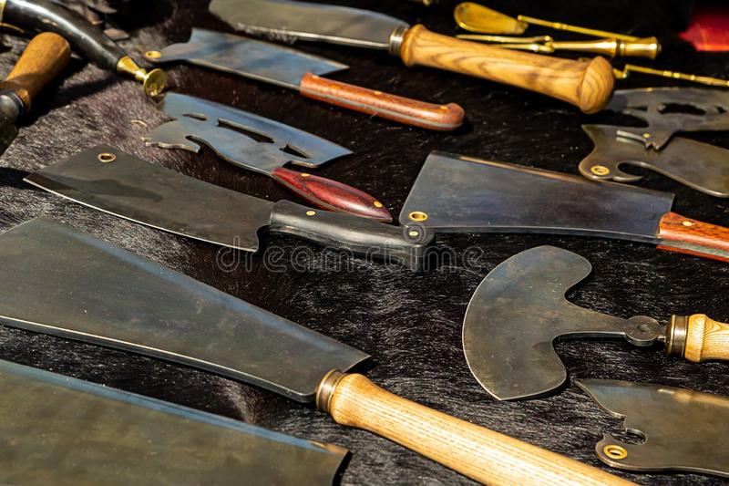 Set of meat knives culinary ax sharpened wide blade choice for every taste on a black background tray gunsmith royalty free stock image