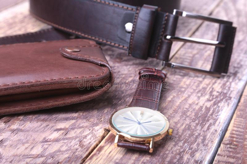 Set of men`s accessories for the business with leather belt, wallet, watch and smoking pipe on a wooden background. The. Concept of fashion and travel stock images