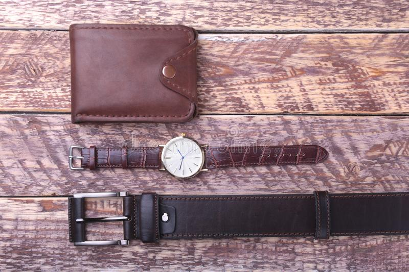 Set of men`s accessories for the business with leather belt, wallet, watch and smoking pipe on a wooden background. The. Concept of fashion and travel royalty free stock photography
