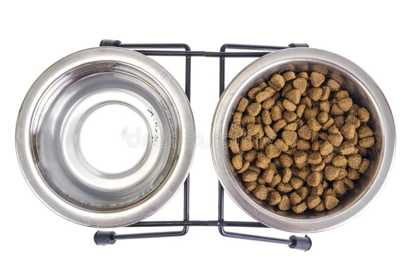 Set of metal bowls of water and dry pet food. stock image