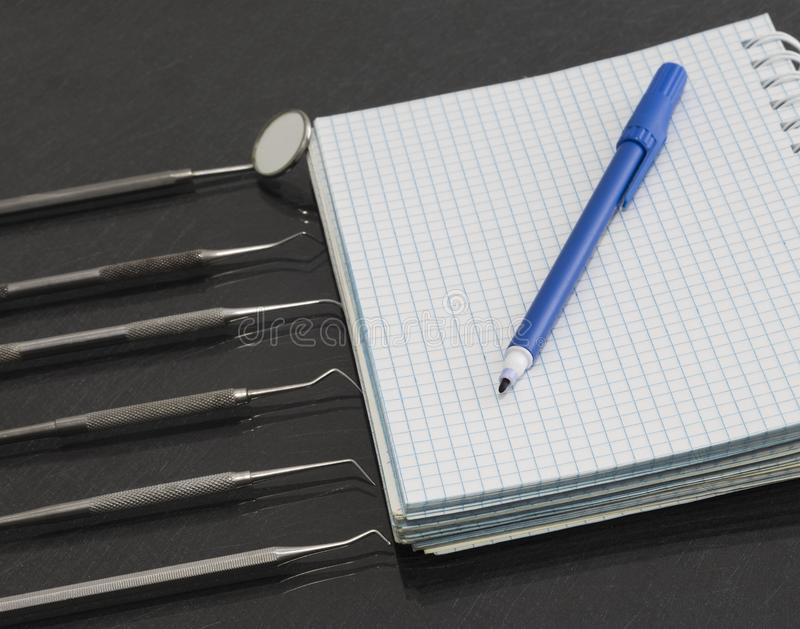 Set of metal Dentist`s medical equipment tools with notebook and marker royalty free stock photo