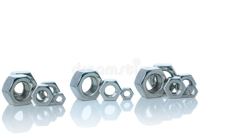 Set of metal hexagon nuts isolated on white background. Small, medium, and big of silver metal hexagon nuts. Hardware tool. Fastener with a threaded hole royalty free stock photo