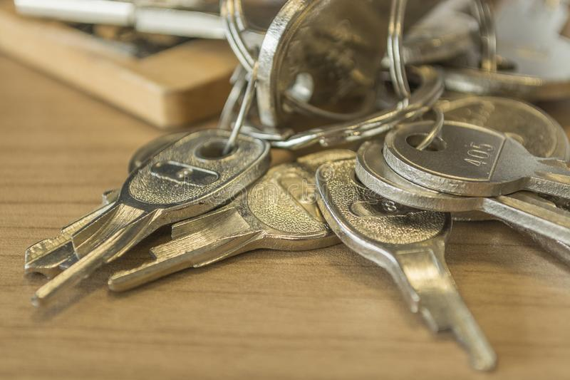 Set of home keys detailed. Set of metallic and detailed home keys on the wood table royalty free stock images