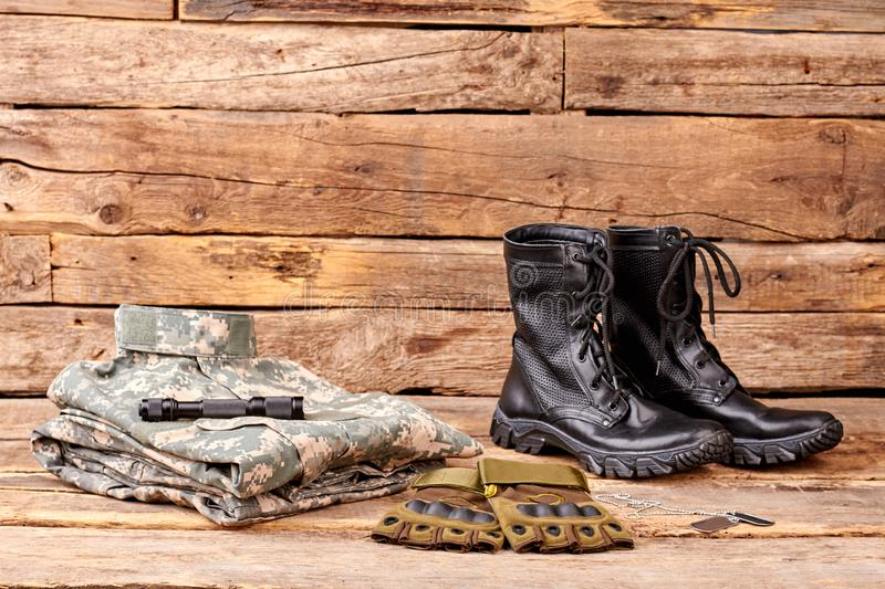 Set of military clothes and equipment. Wooden desk surface background stock photo