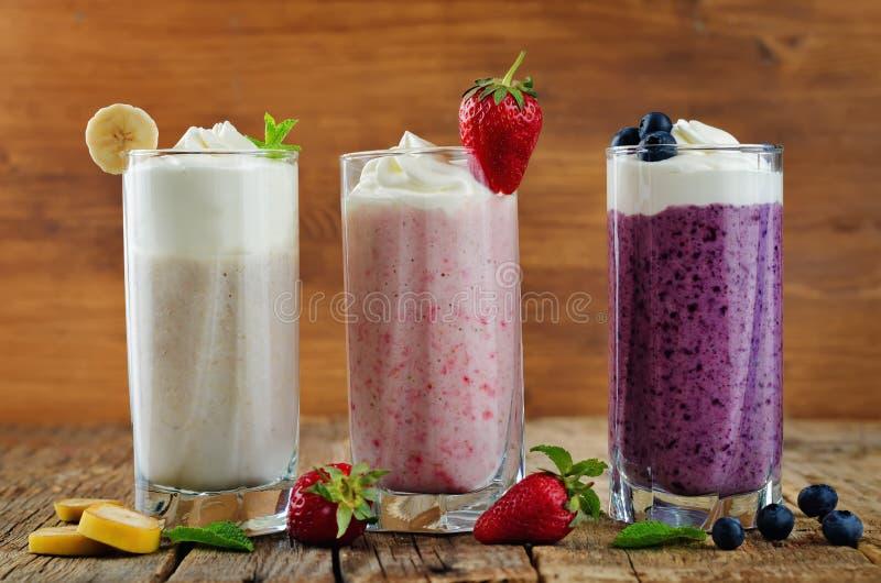 Set of milkshakes: banana, strawberry and blueberry. Toning. selective Focus royalty free stock photography