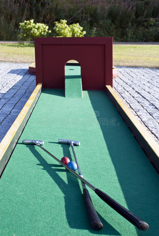 Set of mini golf clubs and color balls on green