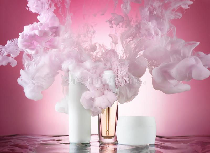 A set of moisturizing cosmetics in a water wave with pink paint clubs around, pink background stock photo